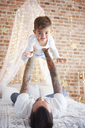 Father lifting up son at Christmas time in bed - ABIF01027