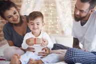Happy family celebrating Christmas in bed - ABIF01030