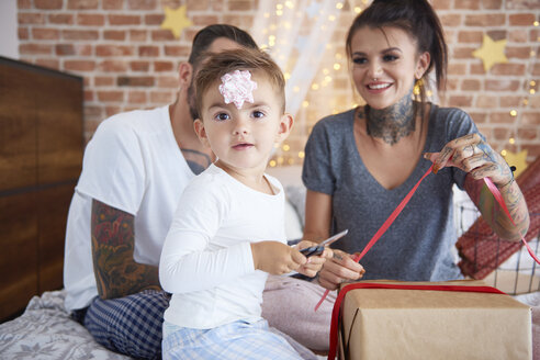 Portrait of boy opening Christmas present with his parents in bed - ABIF01036