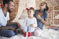 Happy family having fun at Christmas time in bed - ABIF01039