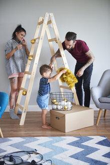 Modern family decorating the home at Christmas time using ladder as Christmas tree - ABIF01054