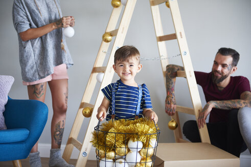 Modern family decorating the home at Christmas time using ladder as Christmas tree - ABIF01057