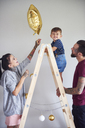 Modern family decorating the home at Christmas time using ladder as Christmas tree - ABIF01060