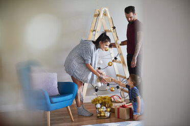 Modern family at home at Christmas time using ladder as Christmas tree - ABIF01066
