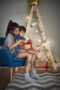 Boy opening Christmas present with his mother at home - ABIF01069