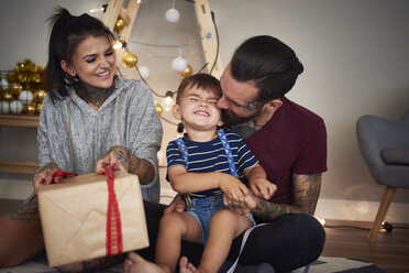 Happy boy opening Christmas present with his parents at home - ABIF01072