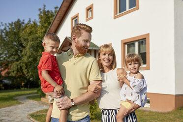 Portrait of happy family in garden of their home - ZEDF01545