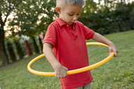 Boy playing with hula hoop in garden - ZEDF01557