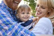 Happy parents hugging her daughter outdoors - ZEDF01563