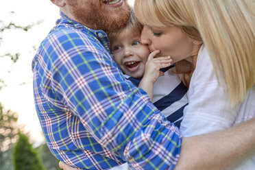 Happy parents hugging her daughter outdoors - ZEDF01566