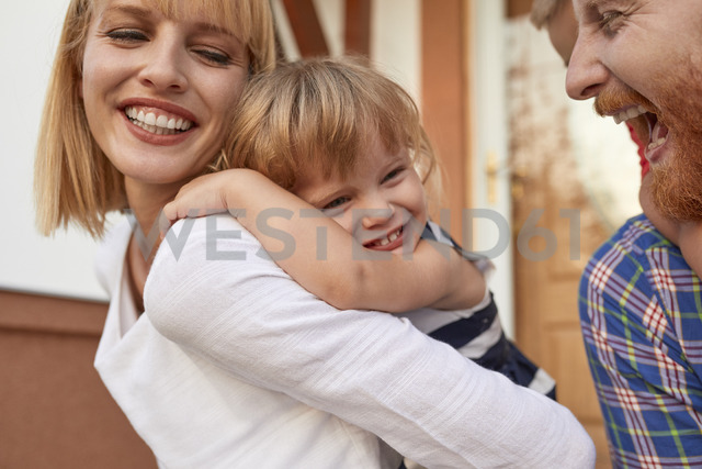 Close-up of happy family in front of their home - ZEDF01572