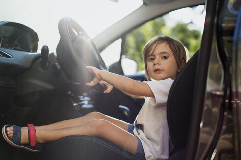 Portrait of little boy sitting on driver's seat in a car - AZOF00054