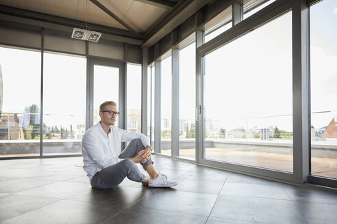 Businessman sitting in empty room looking out of panorama window - RBF06721