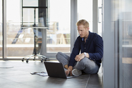 Businessman sitting on the floor using laptop - RBF06730