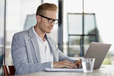 Businessman using laptop on desk in office - RBF06733