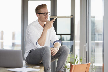 Smiling businessman sitting on desk in office using smartphone - RBF06745