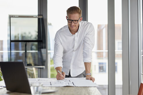Smiling young man working on blueprint on desk in office - RBF06748