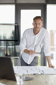 Portrait of smiling young man working on blueprint on desk in office - RBF06751