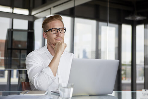 Businessman with laptop on desk in office thinking - RBF06754