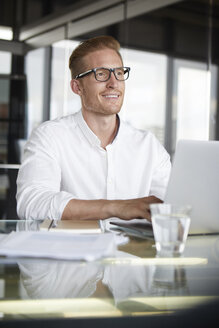 Smiling businessman with laptop on desk in office - RBF06757