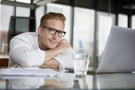 Portrait of smiling businessman leaning on desk in office with laptop - RBF06760