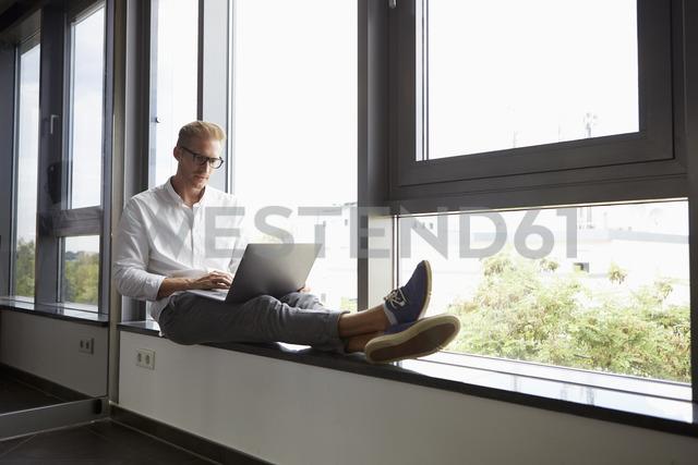Businessman sitting on windowsill using laptop - RBF06769