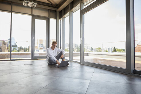 Businessman sitting in empty room with panorama window using laptop - RBF06772