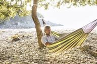 Croatia, Cres Island, man lying in hammock on a beach using laptop - JESF00160