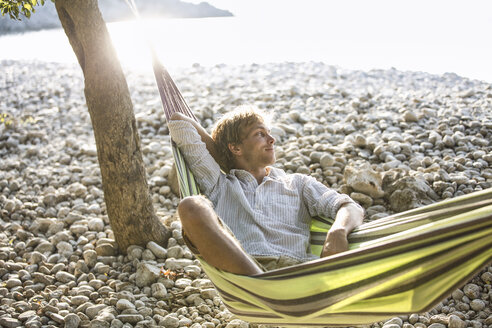 Croatia, Cres Island, content man relaxing in hammock on the beach - JESF00166