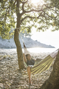 Croatia, Cres Island, woman with laptop relaxing in hammock on a beach - JESF00172