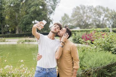 Young gay couple taking selfie with smartphone at city park - FBAF00055