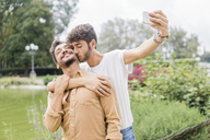 Happy young gay couple taking selfie with smartphone at city park - FBAF00058