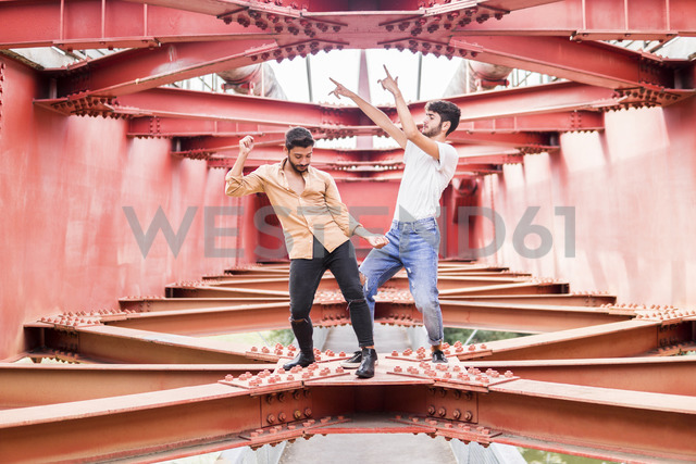 Young gay couple dancing on steel girders of a footbridge - FBAF00073