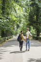 Young gay couple with backpacks walking hand in hand on a road - FBAF00085