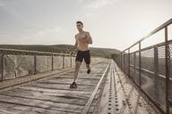Young shirtless man running on bridge - JASF01960