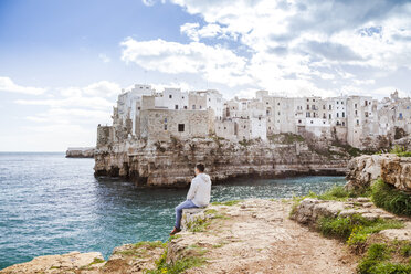 Italy, Puglia, Polognano a Mare, back view of man relaxing on rocks looking at horizon - FLMF00035