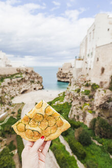 Italy, Puglia, Polognano a Mare, woman's hand holding piece of zucchini focaccia - FLMF00047