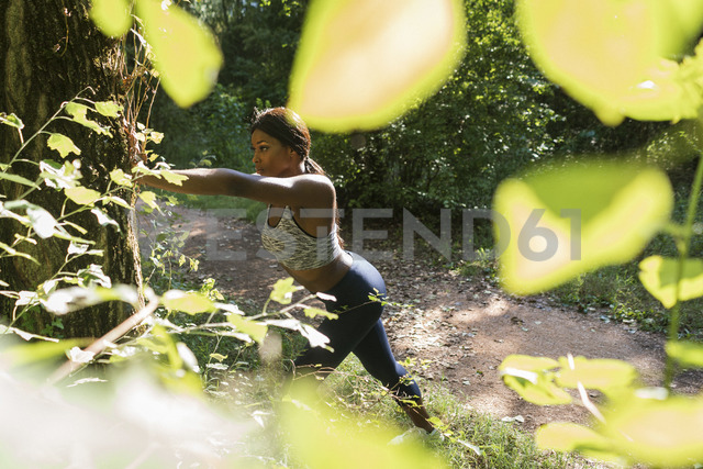 Young athlete taking a break, stretching in the fields - GIOF04445