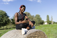 Young athlete sitting on straw bale, listening music with smartphone and headphones - GIOF04451