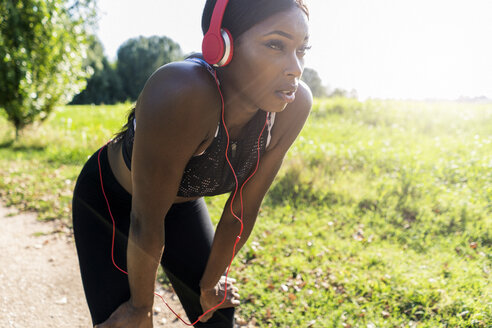 Young athlete in nature, listening music with headphones, preparing for training - GIOF04457