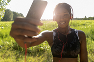 Young athlete in nature, listening music with headphones, holding smartphone - GIOF04469