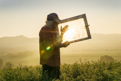 Italy, Tuscany, Borgo San Lorenzo, senior man holding window frame in field at sunrise above rural landscape - FBAF00091