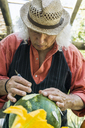 Senior man working on a watermelon with carving tool - FBAF00109