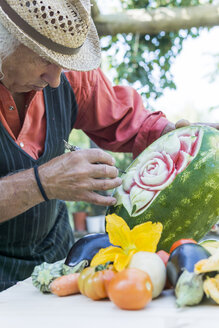 Senior man working on a watermelon with carving tool - FBAF00112