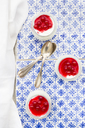 Greek yogurt with red currant sauce on blue patterned tiles - LVF07445