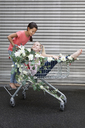 Two girls playing with shopping cart decorated with white artificial flowers - PSTF00173