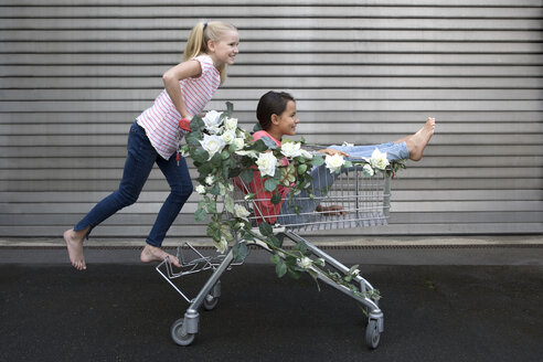 Two girls playing with shopping cart decorated with artificial flowers - PSTF00176