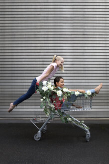 Two girls playing with shopping cart decorated with white artificial flowers - PSTF00179