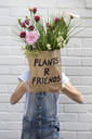 Girl hiding face behind paper bag with flowers - PSTF00182