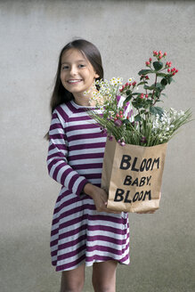 Portrait of smiling girl holding paper bag with flowers - PSTF00188